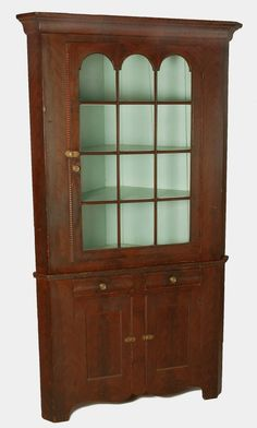 """DESCRIPTION: Two part corner cupboard with bold ogee molding to top. Twelve lite door with arched top lites. Base with two ogee drawers with paneled doors. Grain painted in brown. Shaped skirt. Dauphin County, Pennsylvania. Circa 1820 to 1830. MEASUREMENTS: 48"""" wide x 23"""" deep at top molding x 85-1/2"""". CONDITION: Splitting and minor losses to base molding. Minor paint wear."""