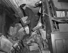 After the bodies of the brothers were found in 1947, cops began digging into the Collyer secrets inside the brownstone. Standing on junk, a cop lifts a box off the floor of the decaying Collyer mansion.
