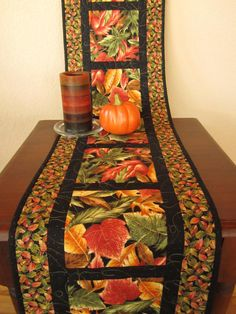 Leaves Table Runner Use up some of that Autumn fabric I've got in the closet. autumn leaves table runnerUse up some of that Autumn fabric I've got in the closet. Quilted Table Runners Christmas, Table Runner And Placemats, Table Runner Pattern, Quilt Placemats, Fall Sewing, Place Mats Quilted, Quilted Table Toppers, Halloween Table, Halloween Quilts