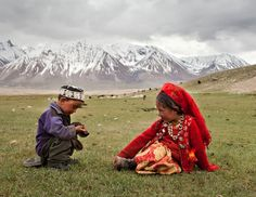 Afghanistan | Two young Afghan Kyrgyz play in the grass in spring. Wakhan | © Matthieu Paley / National Geographic