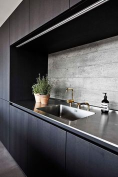 dark wooden cabinets, stained steel countertops and a textural concrete backsplash for a stylish moody look