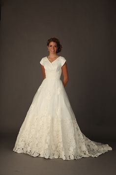 B1109 - Hand cut lace embellishes the hem and natural waistline of this timeless ball gown. The wrapped v neckline is overlaid in delicate organza. - http://www.beautifullymodest.com/products/B1109.html