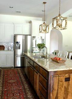Gold lanterns in a white kitchen with vintage oriental rug