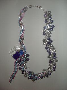 Collar de largo mediano con variedad de perlas en tonos grises y azules con detalles geometricos en acrilico