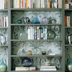 Ever since I repurposed some bookshelves into a media center in our guest studio, I've had bookcase styling on my mind.  I am always drawn to bookcases where the back has been enhanced with paint or wallpaper.  I took a few hours to decorate my own media bookcases in an inexpensive way.     But first, here are a few images that really inspire me.