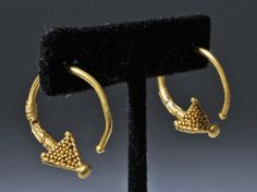 "Nothern Europe, Viking, ca. 9th to 12th century CE. A breathtaking pair of 22+ karat gold hoop earrings adorned with inverted pyramidal terminals which are elaborately dressed in fine and copious granulation. Furthermore, large sections of the hoops are wrapped with gold wiring, making for an elegantly coiled framing of a sinuous or serpentine motif. Size: 8.6 grams for the pair; 1""L (2.54 cm) x 7/8""W (2.22 cm) x 1""W (2.54 cm). <BR><BR> Provenance: Ex-private A. Green collection, United…"