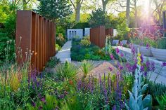 This design incorporating gravel paths, stone structures and low-growing mounds of foliage, would sit equally well in an English garden or somewhere much warmer. The terracotta-colored structures add warm tones to the scene as well as formality, a clever foil for the cool purple flowers.