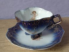 antique flow blue tea cup and saucer set, Victoria Carlsbad Austria demitasse tea set, cherub angel, blue white gold, victorian footed cup