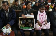 Blessings: People hold the skulls as they wait to be greeted by the priest inside the chapel. The skulls are used as amulets and are believed to offer protection.There is a mixture of Catholic and indigenous traditions in Bolivia