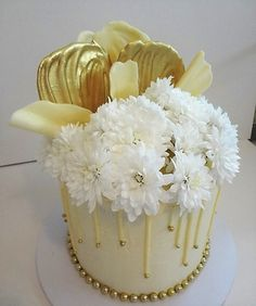 Layers of delicious cake filled and iced with ganache, gold embellished white chocolate drip and sales and snow white chrysanthemums.