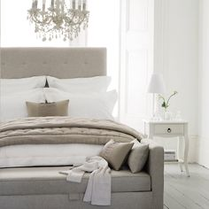 divine bedroom from The White Company with high buttoned headboard, white, beige and palest grey linens and a hint of French - opaque white chandelier and louis table - The Paper Mulberry: White