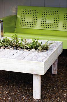 Table de jardin faite avec des palettes en bois. Au centre jardinière plantes aromatiques integrée dans plateau de table