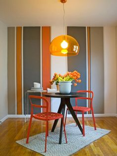 Go Mod -- A striped accent wall is the focal point in this funky dining room design, featuring shades of gray and orange. A modern pendant light hangs over a small black table with metal chairs painted a bright orange.
