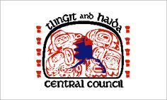 The distinctive style of carving exemplified by the totem pole can be seen in the design of the flag of the Tlingit and Haida Central Council. That flag is white bearing their unusually shaped seal in the center. The edge of the seal is almost rectangular, with the two upper corners rounded off. The black line used to form the outer edge varies in width, getting heavier and heavier as it rises from a very narrow baseline.
