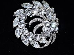Item # 041723  Vintage late Art Deco early Mid Century, circa 1945-50 signed Eisenberg Ice Swarovski crystal glass rhinestone brooch set in rhodium plating. Brooch measures approx 2 1/3 in diameter as it is not symmetrical, but rather a swirling layered and dimensional design.  Condition: Very good antique vintage condition with typical wear due to age and handling. All stones present and have a stunning clarity. Upon very close inspection there is one tip of one marquise navette which h...