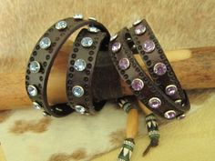 Hand stamped and dyed double wrap bracelets with a variety of colors of crystal rivets to choose from.  Will fit 6 to 7 inch wrists and closes with a button stud.  Made in the USA by Stones River Leather. Available now at stonesriverleather.com  $50.00