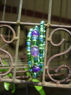 Memory wire bracelet with purple, blue and green beads from Charming Spirals. This would be the perfect accessory for Mardi Gras! #scottsmarketplace