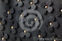 Black leather background with decorative flowers and studs.