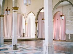 Vintage brass light fixtures, peeling paint and soft hues with tall arches at this historic dream venue space in New Orleans. Matoli Keely Photography