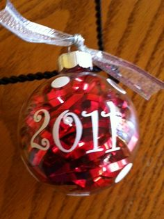 Clear glass ornament with tinsel and vinyl initial, year, and polka-dots