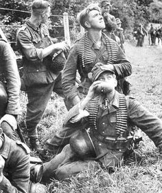 Normandy June 1944: German troops during a lull glance at the sky as Allied aircraft fly over.