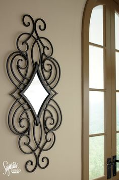 Adding simple elegance to your home is easy with this matte black finished metal mirror. The diamond shaped scroll design dresses up any wall in a snap. #AshleyFurniture - Wall Decor & Accessories - Mirrors - Ashley Furniture