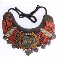 A stunning vintage or antique Tibetan collar studded with gemstones and silver. The centerpiece is a silver Gau box with inset repousse decor and a center and border of turquoise stones. The Gau box is surrounded with rows of amber, coral, turquoise freshwater pearls These beads are sewn onto a padded fabric collar with ties of twisted natural wool . The ends of the collar have sewn silver ornamental rectangles with carnelian center stone and bordered with turquoise stones. From the bottom…