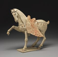A LARGE PAINTED POTTERY FIGURE OF A PRANCING HORSE,TANG DYNASTY. -- Sotheby's