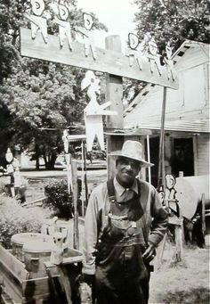"Herman Bridgers  Born 1912  In front of his ""churchmen"" figures  in front of his house   1988"