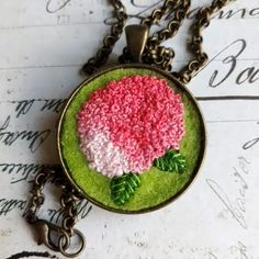 "Hand-embroidered romantic necklace with a hydrangea flower.  The necklace is made of an antique bronze-colored base and a chain and decorated with a cabochon with a pink hydrangea. The flower was hand-embroidered on a green felt with embroidery threads.  Each work is unique because it is made from beginning to end by hand!  The diameter of the pendant: 3,3 cm = 1.30"". The length of the chain: 55 cm = 21.65"".  My jewelry is created in a non-smoking environment. Embroidery Fashion, Embroidery Jewelry, Embroidery Thread, Beaded Embroidery, Hydrangea Flower, Pink Flowers, Handmade Items, Handmade Gifts, Hand Applique"