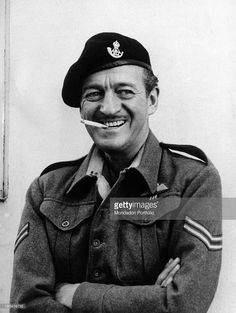 Half-length portrait of the smiling English actor David Niven, smoking a cigarette and dressing the part of corporal of the light artillery John Antony Miller in a scene from the war movie The Guns of Navarone, by English director J. Lee Thompson. 1960.