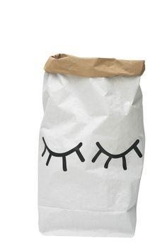 Spielzeugsack aus Papier Motiv: geschlossene Augen schwarzer Print auf weißem Grund Innenseite: Braun handgedruckt Maße: 55 x 22 x 80 cm Material: Papier