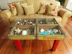 Four old wooden soda crates make a combination coffee table and shadow box. The crates were attached to an old table base, then a piece of tempered glass is laid over top.
