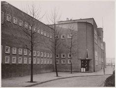 1936 - 1940. Betondorp Zuivelplein met de Rosenburgh school gezien vanuit de Weidestraat. De school is ontworpen door architect Nico Lansdorp en werd geopend in 1924. In 1936/37 werd de school een katholieke kerk en nog later een verenigingsgebouw. Ik ben er nog bij de welpen geweest.