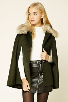 A wool-blend cape featuring a removable faux fur collar a button front, slanted pockets, and a boxy silhouette.
