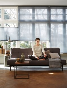 Make a stylish living room statement by gently filtering sunlight through layers of translucent fabric. ♦ Hunter Douglas window treatments