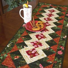 This jolly table runner quilt pattern is a joy to make and will help you to celebrate with good cheer with you and yours. The easy-to-piece blocks in Hot Toddy, by Patricia Bochey, create a lovely and festive centerpiece for your holiday entertaining.