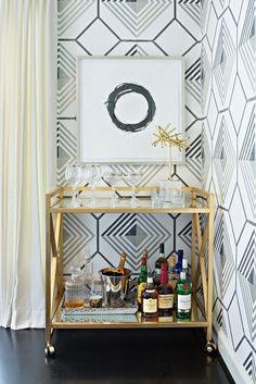 home interior, gold bar cart, framed art, geometric wallpaper