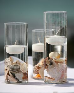 Cylinder Vases, Floating Candles and seashells for an ocean themed centerpiece- Beautiful!. Perfect for the Little Mermaid table at my birthday party a year from now! XD