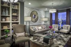 This photo is of a model home designed by Mary Cooke & Associates. Michigan Homes Mayfair Uptown Belmont featuring the Singapore Mirror Large Round Mirror, Round Mirrors, Living Room Mirrors, Living Room Decor, Living Rooms, Hardwood Floors, Flooring, Elegant Living Room, Bookshelves Built In