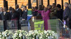 "Archbishop Desmond Tutu addresses the stadium, asking the crowd to be quiet - he ""wants to hear a pin drop"" - at the memorial service for Nelson Mandela. Winnie Mandela, John Major, African National Congress, Jacob Zuma, Desmond Tutu, Hillary Rodham Clinton, Tony Blair, British Prime Ministers, David Cameron"