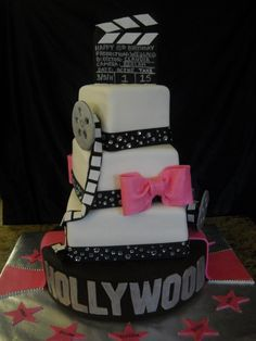 A hollywood themed cake prepared for a quinceanera in south Texas.  Cake featured fondant topper and reels.  Cake was placed on a spinning cake stand to give everyone a view of the cake.
