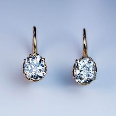 Antique Russian Solitaire Diamond Earrings, St. Petersburg, circa 1890. 14K gold antique earrings are prong set with two sparkling old cushion cut diamonds 0.73 ct and 0.78 ct.