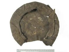 From Museum of London: Flat knitted cap with brim and part of crown cut away from the 16th century. It was knitted in the round in stocking stitch on 4 or 5 needles, then fulled (washed, beaten and felted) and napped (raising and trimming the pile) to produce a stiff, hardwearing fabric. Please see below for further cataloguing details.