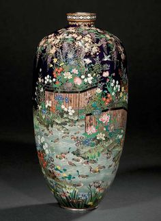 A CLOISONNÉ VASE  SIGNED MURASE ZO, MEIJI PERIOD (LATE 19TH CENTURY)  Worked in various thicknesses of silver wire, polished silver leaf with numerous ducks, crested grebe and other birds in a meandering stream, the river bank with fences surrounding scattered flowers and foliage beneath a cherry tree entwined with wisteria, copper and silvered mounts 24cm. high