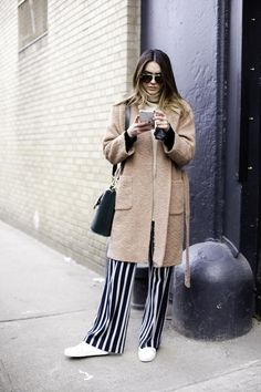 Camel colored coatigan styled with a turtleneck, striped wide leg pants, and clean white sneakers | Street Style from New York Fashion Week Fall 2016 @stylecaster