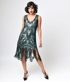 This is an amazing reproduction flapper dress that is simply stunning. It is all hand beaded in glass beads, with a gorgeous beaded pattern throughout with a plunging V neckline and a low drop waist. It has thick beaded tassels that hang below the knee.