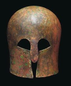 Corinthian helmet, late 7th century B.C. Of high domed form, with narrow everted flange at rear and long nose-guard, pierced with multiple holes around helmet perimeter, restoration to nose-guard, 22.5 cm high. Private collection, from Christie's auction
