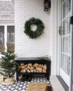 Outdoor holiday nook with a small patio Christmas tree, wreath and fire wood