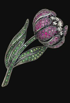 A gem-set flower brooch Pavé-set throughout with circular-cut green garnet and pink sapphires, the stamen set with brilliant-cut diamonds, 7.0 cm long